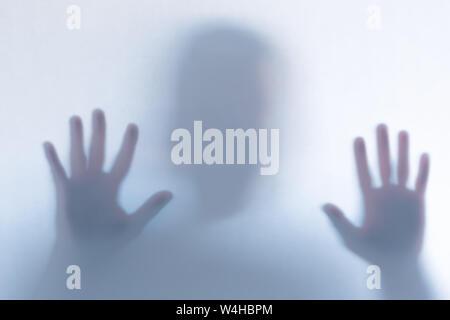 Silhouette fantôme effrayant brouillée derrière un fond en verre blanc. L'orientation horizontale Banque D'Images