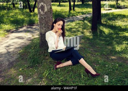 Business woman eating apple sous l'arbre et travailler sur son portable, Selective focus Banque D'Images
