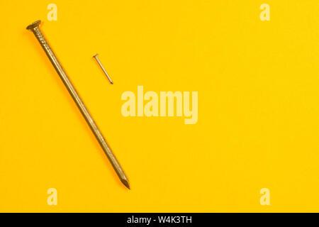 Des clous en métal isolé sur fond jaune Banque D'Images