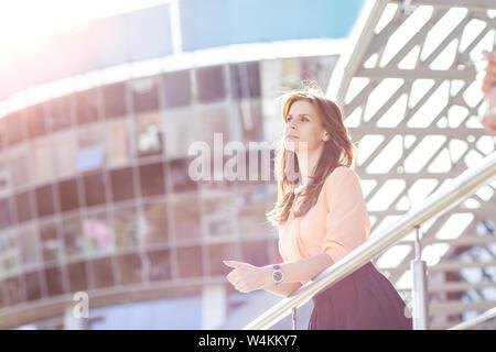Business Woman debout sur le balcon de l'office moderne et regarde dans la distance.La photo a un espace vide pour votre texte Banque D'Images