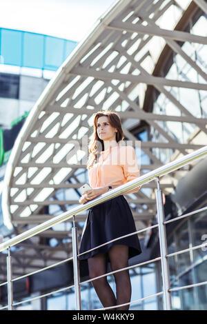 Business Woman debout sur le balcon de l'office moderne et regarde dans la distance.La photo a un espace vide pour votre texte