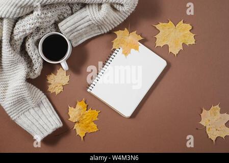 Espace de travail avec feuilles d'érable dorées, ordinateur portable, tasse de café, un chandail sur fond brun. La composition créative. Automne ou Hiver concept. Télévision lay, top v Banque D'Images