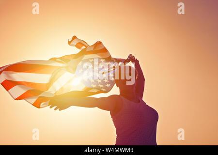 Silhouette of woman in sunglasses avec des mains et en agitant un drapeau des États-Unis d'Amérique contre sunset sky, tonique Banque D'Images