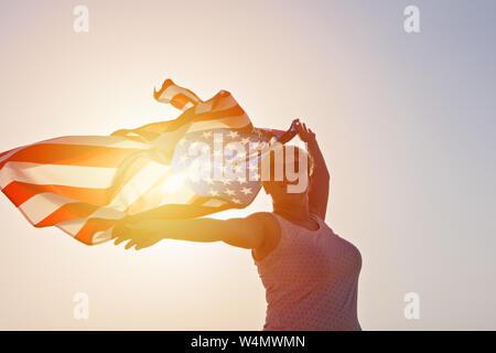 Silhouette of woman in sunglasses avec des mains et en agitant un drapeau des États-Unis d'Amérique contre sunset sky Banque D'Images