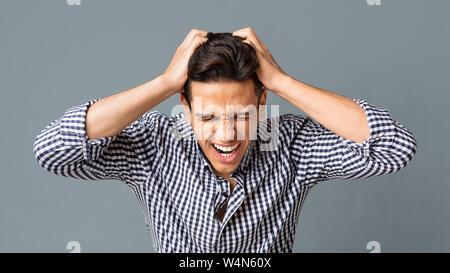 Jeune homme frustré tirant ses cheveux en arrière-plan gris Banque D'Images