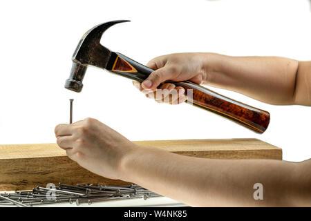 Main hoiding dame hammer hitting un clou à fond blanc Banque D'Images