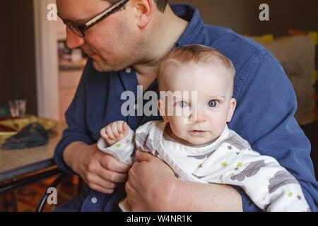 Un bébé aux yeux brillants est assis dans sa tour du père lors d'une table de salle à manger Banque D'Images