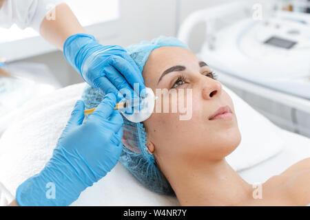 L'esthéticienne professionnelle rend les injections de vitamine de rajeunissement de la peau du visage du patient. Une jeune fille est en cours de traitement de spa