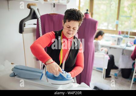 Senior woman with glasses planche une robe dans un studio de design de mode Banque D'Images