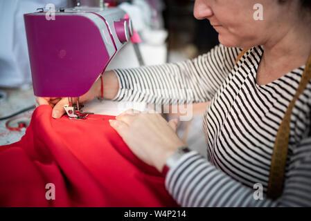 De gros plan femme adultes couturière coud des vêtements et mettre thread dans etui aiguill Banque D'Images