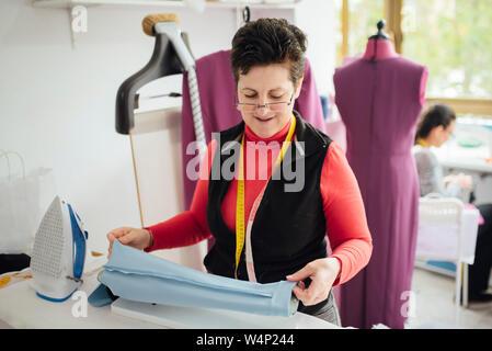 La haute et joyeuse femme planche dans un studio de design de mode Banque D'Images