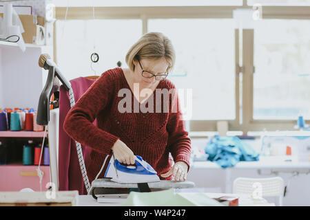 Femme plus âgée, avec des lunettes planche dans un studio de design de mode Banque D'Images