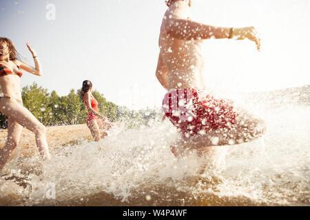 Groupe d'amis heureux court dans l'eau - les personnes actives s'amusant sur la plage en vacances Banque D'Images