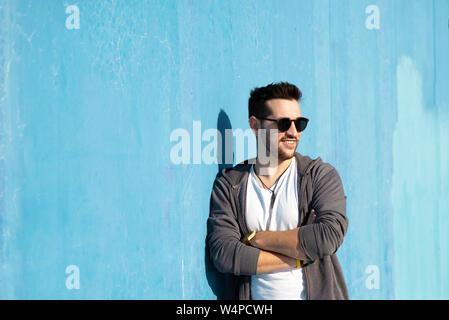 Portrait de jeune homme barbu avec des lunettes leaning against wall Banque D'Images