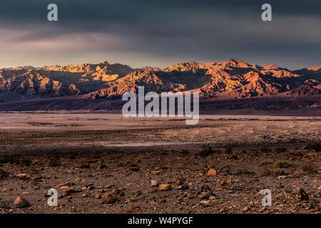 Le coucher du soleil illuminant les montagnes funéraire dans la vallée de la mort avec Mesquite Flat dunes de sable à l'avant-plan. Banque D'Images