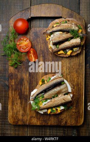 Sandwichs appétissants avec anchois et oeufs sur fond de bois, vue du dessus Banque D'Images