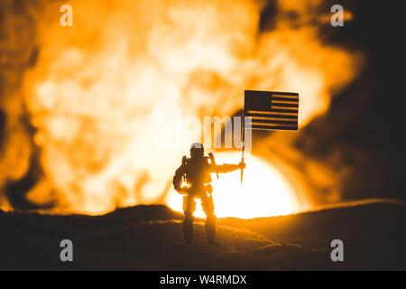 Toy Soldier silhouette avec le drapeau américain sur la planète avec Sun en fumée Banque D'Images