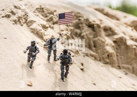 Toy Soldiers avec arme debout sur le sable et holding american flag Banque D'Images
