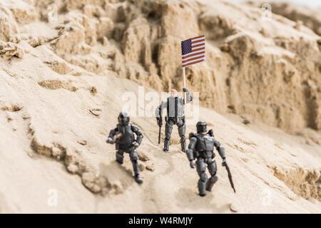 Des soldats armés de jouets sur le sable et tenant un drapeau américain Banque D'Images