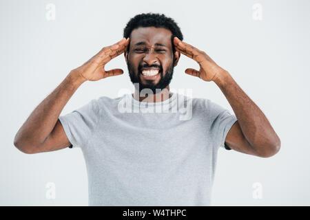 African American man mal de tête après avoir isolé sur gray Banque D'Images