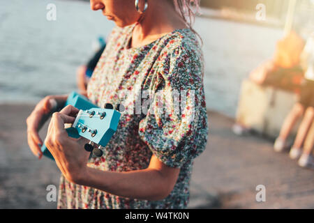 Rogner la photo du musicien romantique jeune femme africaine avec des tresses en jouant sur robe ukulele sur le coucher de soleil sur la plage