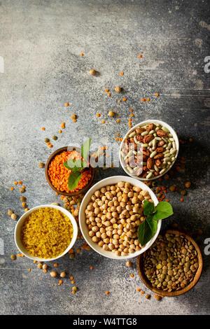 L'alimentation saine, les régimes, la nutrition concept, source de protéines végétaliennes. Des matières premières les légumineuses (pois chiches, lentilles rouges, les lentilles, haricots, pois chiche, boulgour). À Banque D'Images