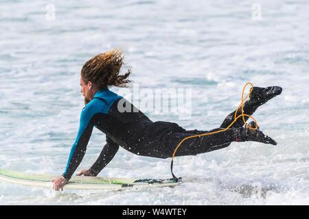 Un surfeur homme lancer lui-même et sa planche de surf dans la mer à Newquay dans Fistral à Cornwall. Banque D'Images