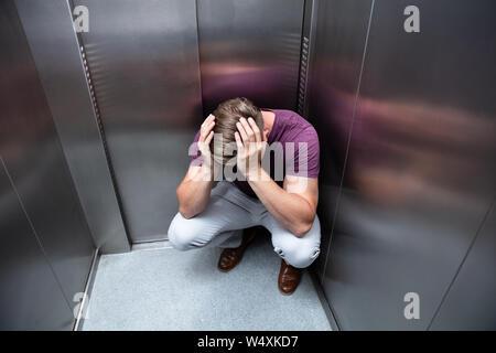 L'homme inquiet accroupi avec les mains sur la tête de l'élévateur Banque D'Images
