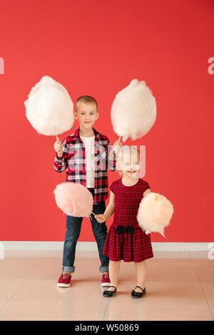 Cute little children avec Cotton Candy contre mur couleur Banque D'Images