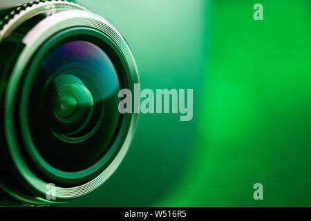 Objectif de l'appareil photo à rétroéclairage vert. Vue de côté de l'objectif de l'appareil photo sur fond vert. Greencamera Lens Close Up. Rouge pur Banque D'Images