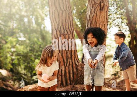 L'éclatement des filles les ballons d'eau avec les mains dans un parc. Groupe d'enfants s'amusant dans la forêt.