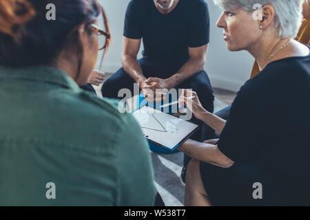 Femme d'affaires à maturité expliquant la stratégie de l'équipe en réunion. Groupe multi-ethnique de personnes siégeant ensemble avoir une réunion.