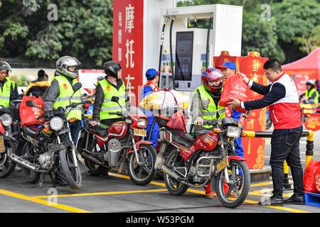 Travailleurs migrants chinois queue pour avoir leurs motos à être ravitaillés en libre dans une station de comme ils monter des motos sur leur chemin de retour pour Banque D'Images