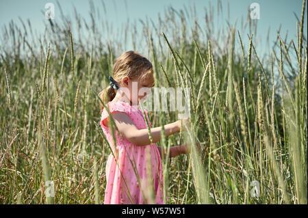 Vue de côté de l'accent adorable petite fille en robe rose standing in field sur l'Islande 1735 Island et la tenue d'herbe Banque D'Images