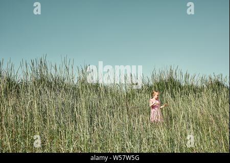Jolie jeune fille en robe rose de marcher dans l'herbe haute dans un écrin de verdure au soleil sur l'île en été 1735 Banque D'Images