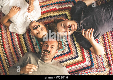 Son père et ses deux fils bénéficiant ainsi allongé sur une couverture en couleur. Les hommes d'arbres d'âges différents smiling jouer avec fake moustache. Vue de dessus d'un couple
