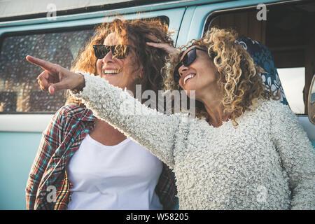 Happy friends holding les uns les autres, deux belles femmes d'âge moyen souriant avec des lunettes. Pretty Girls having fun beach, parfait début de vacances sur