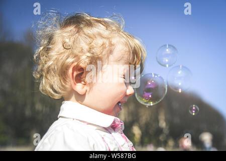 Belle petite fille cheveux brun, a fun heureux visage souriant, jolie yeux, cheveux courts, jouer et attraper des bulles de savon en été la nature, habillé wh Banque D'Images