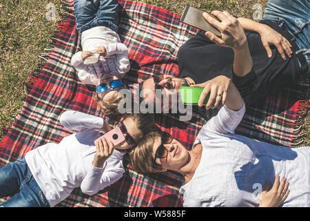 Les jeunes professionnels famille joue autoportraits avec téléphones mobiles. maman papa et deux petites filles blague amusé avec lunettes de soleil et discuter entre eux. concept o