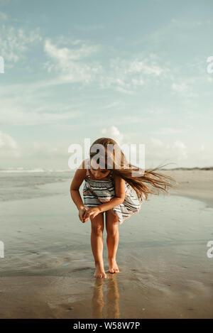 Petite fille à la recherche des coquillages sur la plage de Corpus Christi au Texas