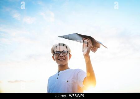 Heureux l'enfant jouer avec avion en papier au coucher du soleil, le rêve de voler, l'avion en main et ciel bleu avec des nuages et du soleil. Garçon s'amuser au cours de soleil Banque D'Images