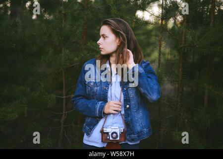 Woman hand holding retro camera. Jeune fille hipster photographe avec appareil photo. Jeune femme photographe. Banque D'Images