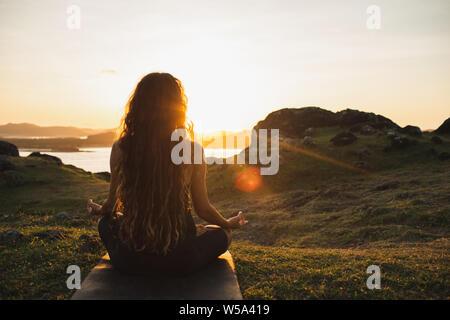 Woman meditating yoga seul au lever du soleil sur les montagnes. Vue de derrière. Style de voyage relaxation spirituelle concept. Harmonie avec la nature.