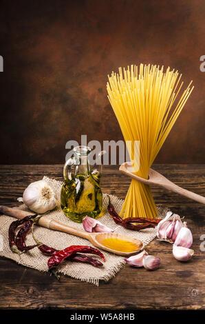 La vie encore. Spaghetti à l'ail cru, certains et piments forts séchés huile d'olive sur la table en bois brut Banque D'Images
