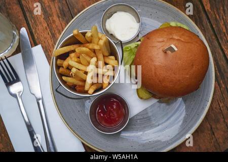 Vue rapprochée d'un burger de boeuf au fromage, cornichons, la laitue et les oignons avec un frites et ketchup et sauces mayo. Le format paysage. Banque D'Images