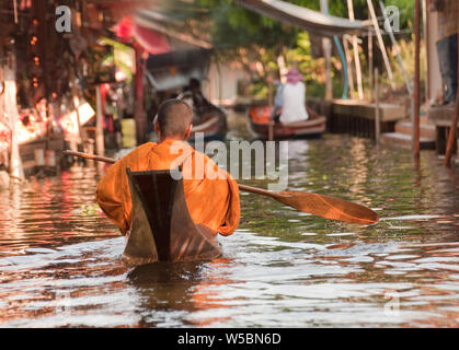 Un Monkin bouddhiste traditionnelle dans une pirogue à la très populaire au marché flottant de Damnoen Saduak près de Bangkok en Thaïlande en Asie une grande Gam Banque D'Images