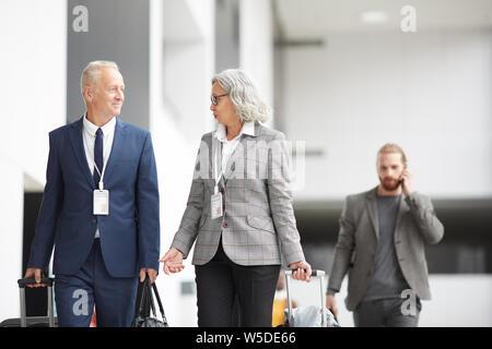 Confiant de contenu multi-ethnique mature aux participants au forum de soirée marcher avec des valises et bavarder tout en laissant airport Banque D'Images