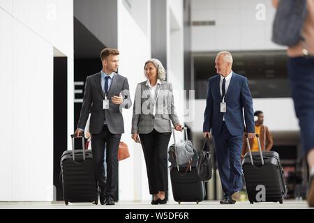 L'équipe de confiance aux participants au forum de soirée transportant des valises à roulettes et l'aéroport de passage ensemble guide Banque D'Images