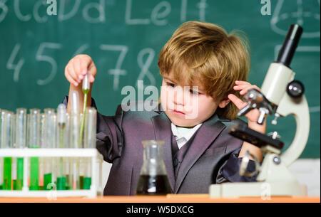 Petit garçon à leçon. Retour à l'école. Petit garçon fait des expériences scientifiques. la science biologie scientifique pour enfants. Des études scientifiques. Les expériences Scientifiques avec microscope en laboratoire. L'amélioration de la médecine moderne. Banque D'Images