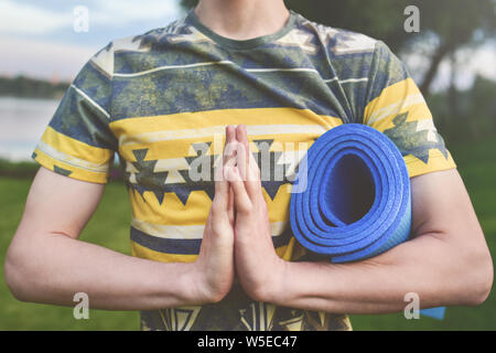 Le yoga. Close up les hommes de mains. Les jeunes hommes faire du yoga en plein air sur mat.Guy l'exercice de yoga sur le jardin.Les jeunes hommes méditant dans la posture du lotus zen. Gros plan Banque D'Images